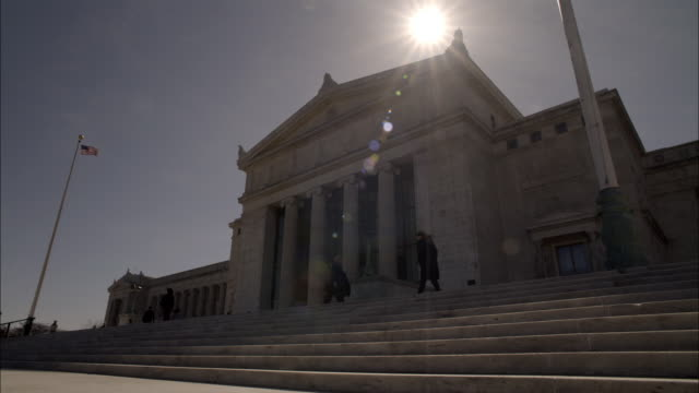 pull back of stone government office building. could be courthouse. marble columns or pillars. people standing on steps. american flag in bg. - palazzo di giustizia video stock e b–roll