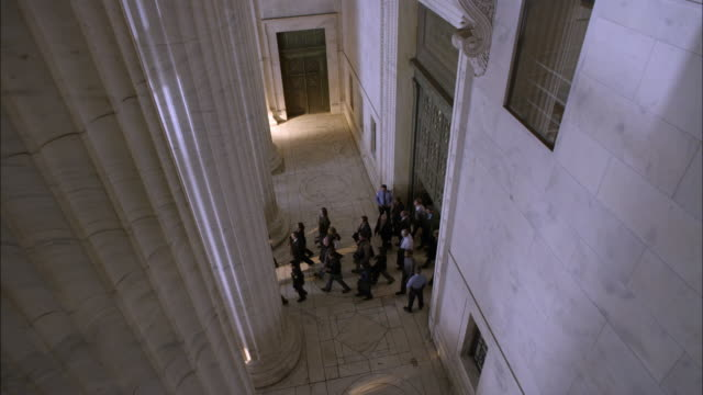 high angle down of crowd of people exiting into portico of marble stone government office building or courthouse. marble columns or pillars. lawyers and reporters. - avvocato video stock e b–roll