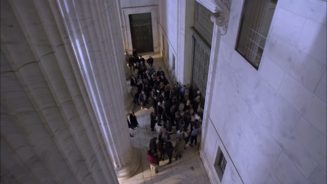 high angle down of crowd of people entering from portico into marble stone government office building or courthouse. marble columns or pillars. lawyers and reporters. - government building stock videos and b-roll footage