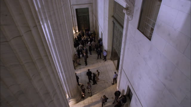 high angle down of crowd of people exiting into portico of marble stone government office building or courthouse and then entering building again. marble columns or pillars. lawyers and reporters. - lawyer stock videos & royalty-free footage