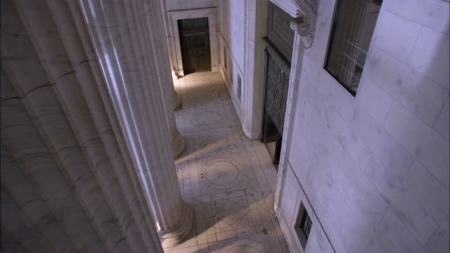 HIGH ANGLE DOWN OF PORTICO OF MARBLE STONE GOVERNMENT OFFICE BUILDING OR COURTHOUSE. MARBLE COLUMNS OR PILLARS.