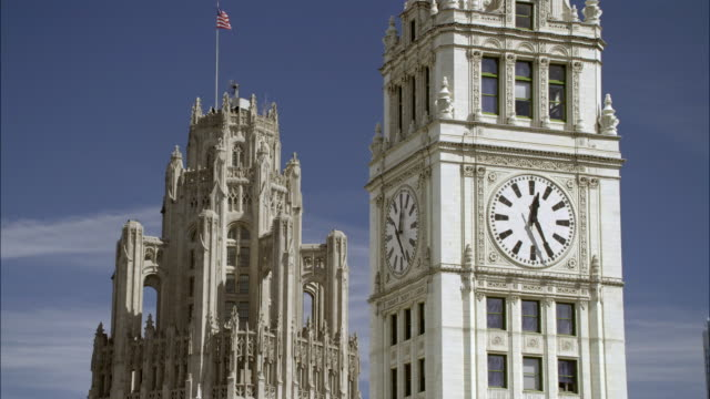 WIDE ANGLE OF TOP OF TRIBUNE TOWER AND CLOCK TOWER ON WRIGLEY BUILDING. SKYSCRAPERS OR HIGH RISE OFFICE BUILDINGS.