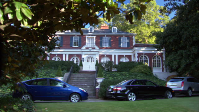 wide angle of upper class estate house or mansion surrounded by trees. cars parked in driveway in front of house. multi -story brick house with many windows. could be residential area or neighborhood in suburbs. - upper class stock videos & royalty-free footage