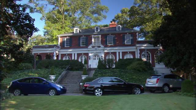 wide angle of upper class estate house or mansion surrounded by trees. cars parked in driveway in front of house. multi-story brick house with many windows. could be residential area or neighborhood in suburbs. - upper class stock videos & royalty-free footage