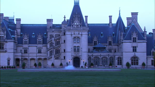 "MEDIUM ANGLE OF BILTMORE ESTATE. UPPER CLASS CASTLE. COULD BE MANSION OR ESTATE HOUSE. MULTI-STORY. FOUNTAIN VISIBLE IN FRONT OF HOUSE. CAR PULLS UP TO HOUSE FROM LONG DRIVEWAY.<P><A HREF=""HTTPS://WWW.SONYPICTURESSTOCKFOOTAGE.COM/FOOTAGE?KID=4271"">FOR DAY"