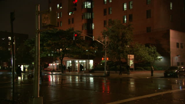 WIDE ANGLE OF MULTI-STORY HOSPITAL WITH AMBULANCE PARKED IN FRONT. STREETS WET FROM RAIN. ENTRANCE OF HOSPITAL ILLUMINATED. TREES OUT FRONT.