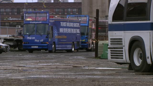 wide angle of double-decker buses parked in parking lot. industrial area. - dubbeldäckarbuss bildbanksvideor och videomaterial från bakom kulisserna