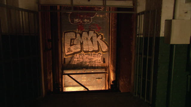 medium angle of lights flickering at bottom of freight elevator shaft as if from fire. graffiti. lower class building. - freight elevator stock videos & royalty-free footage