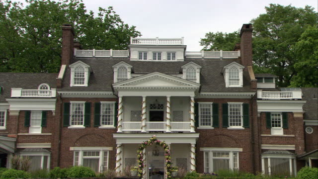 wide angle of three-story upper class brick house or mansion. flowers in garden. could be decorated for a wedding. - brick house stock videos and b-roll footage