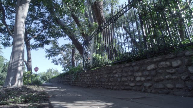 wide angle of sidewalk in residential area or neighborhood in suburbs. wrought iron fence visible in fg. trees. stop sign visible in bg. - カリフォルニア州 パサデナ点の映像素材/bロール