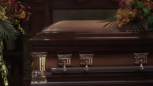 close angle of flowers next to and laid upon coffin. could be funeral or funeral home. - 棺点の映像素材/bロール