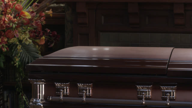 close angle of flowers next to coffin. could be funeral or funeral home. - coffin stock videos & royalty-free footage