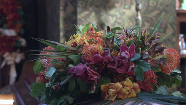 close angle of wreath of flowers. could be on coffin. could be funeral or funeral home. - coffin stock videos & royalty-free footage