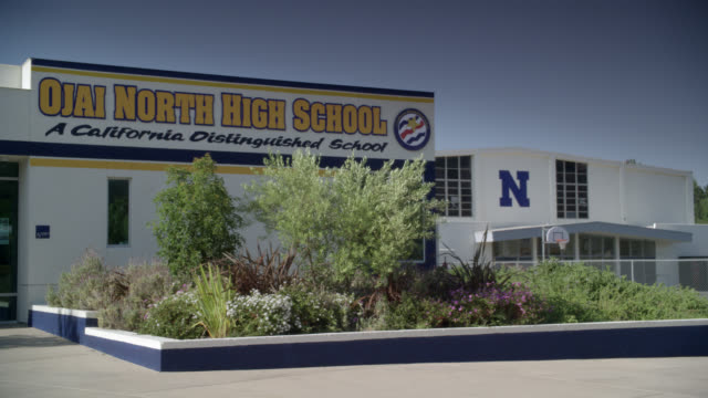 "wide angle of high school entrance. sign on building reads ""ojai north high school a california distinguished school."" actual location is nordoff high school. plants and flowers visible at entrance. gymnasium or building visible in bg. basketball hoop vis - entrance stock videos & royalty-free footage"