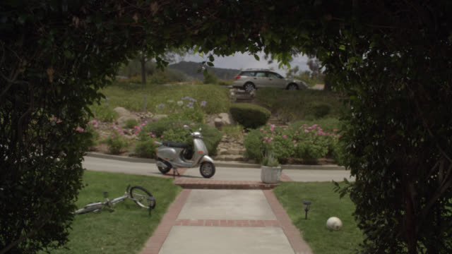 vidéos et rushes de medium angle of sidewalk or walkway leading under arched bushes or shrubs. bicycle and ball visible on lawn. could be front yard. car parked on curb in bg. flower and plants. vespa or moped parked at head of sidewalk. - vespa