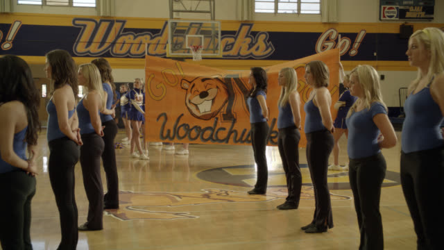 """PAN UP FROM WIDE ANGLE OF DANCE TEAM OR CHEERLEADERS DURING PEP RALLY TO SIGN OR BANNER READING """"GO WOODCHUCKS GO!"""" COULD BE HIGH SCHOOL. GYMNASIUM. BASKETBALL HOOPS VISIBLE. GIRLS DANCE AND SMILE."""