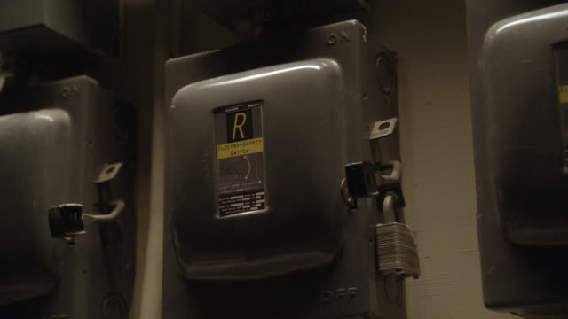 close angle of hand pushing up lever on circuit breaker or power boxes with locks or padlocks. could be basement. - lever stock videos & royalty-free footage