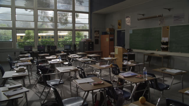 wide angle of empty school classroom with desks. books and notebooks. chalkboards. - 教室点の映像素材/bロール