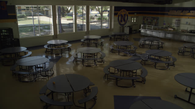 high angle down of empty tables in high school cafeteria. - cafeteria bildbanksvideor och videomaterial från bakom kulisserna