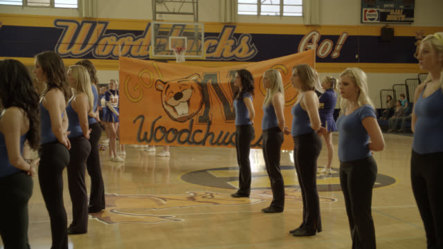 MEDIUM ANGLE OF DANCERS AT PEP RALLY IN HIGH SCHOOL GYM. SIGN FOR WOODCHUCKS. MASCOT.