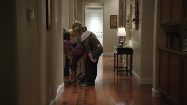 vídeos de stock e filmes b-roll de wide angle of kids standing in group in front of door in hallway. upper class house. table with lamp visible. kid runs down hallway and group follows. several individual kids follow. could be playing or game. - corredor caraterística de construção