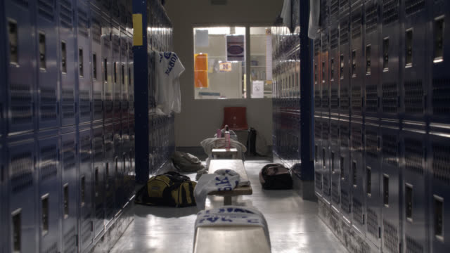 vidéos et rushes de wide angle of locker room in gym with towels thrown on benches. bags visible on floor. office in bg. could be high school. - serviette de bain