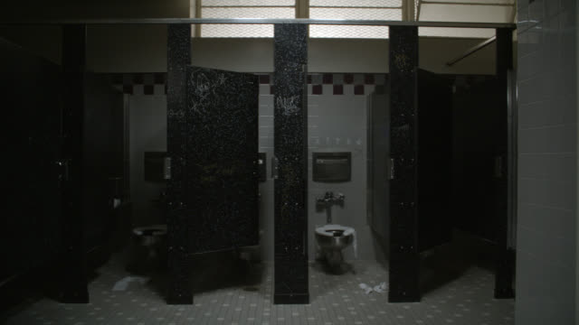wide angle of bathroom stalls. could be high school. graffiti and writing on walls. toilet paper strewn on floor. - bathroom stock videos & royalty-free footage