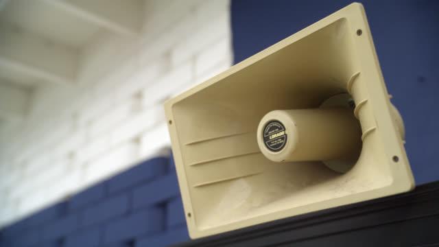 vídeos y material grabado en eventos de stock de close angle of loud speaker on wall. cinderblock wall in bg. - altavoz