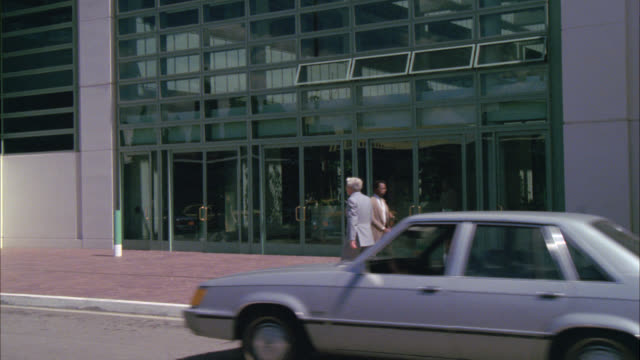 stockvideo's en b-roll-footage met pan up of high rise office building   around 20 floors. could be new york or los angeles. modern glass exterior. 1292-g same shot but pans down to entrance. - 1987