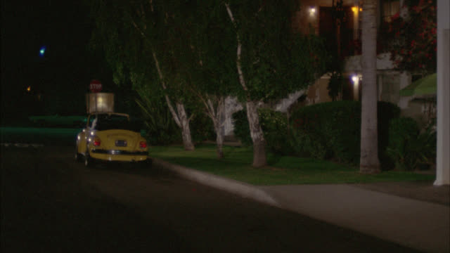medium angle of volkswagen car parked in front of two story apartment building. red car pulls up and man get out exits. - volkswagen stock-videos und b-roll-filmmaterial