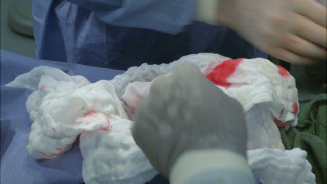 close angle of open wound or cavity in patient in operating room. bloody gauze. doctors or surgeons with scrubs and gloved hands use medical equip mental. surgical tools. - ガーゼ点の映像素材/bロール