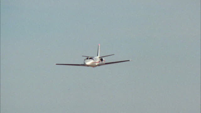 WIDE ANGLE OF TWIN ENGINE CESSNA PLANE FLYING. COULD BE LANDING.