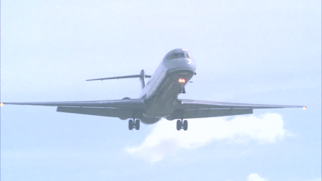 vidéos et rushes de medium angle of commercial jet, airliner, airplane, or plane descending as if preparing for landing. blue sky and clouds. commercial airplane or jet lands on runway. houses, trees, and buildings on hill at end of airstrip. airports. - atterrir