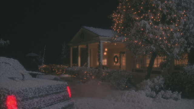wide angle of one story middle class house with porch and wreath on front door. lights on in living room. christmas lights decorate trees and hedges outside house. snowing. limo parke out front. man with umbrella leaves front porch of house and returns to - illinois stock videos and b-roll footage