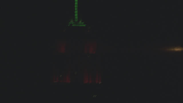 medium angle of lighted spire on empire state building.  red and green christmas colors. - spire stock videos & royalty-free footage