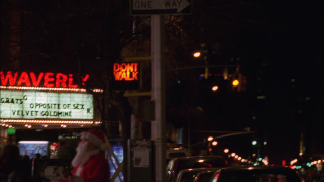 pan up from shot of pedestrians on sidewalk to lighted spire of empire state building. man in santa claus suit ringing a bell. marquee for waverly theater. christmas. stoplight changes. camera pans back down to sidewalk. - spire stock videos & royalty-free footage