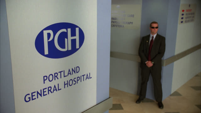 vídeos y material grabado en eventos de stock de medium angle of secret service detail wheeling man out of hospital on a gurney. portland hospital. - portland oregón