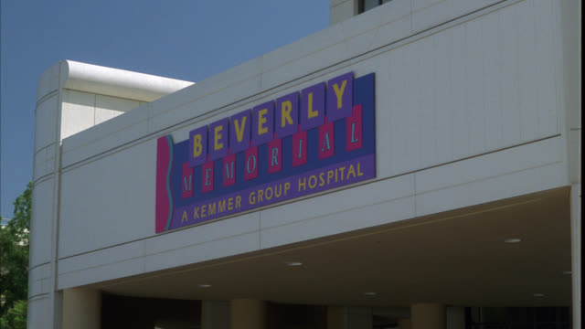 """stockvideo's en b-roll-footage met medium angle of sign above entrance to hospital that reads """"beverly memorial a kemmer group hospital"""". modern building. - 1991"""