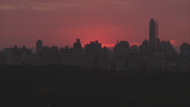 vídeos y material grabado en eventos de stock de wide angle of silhouettes of high rise office, apartment or condominium buildings of new york city skyline. central park in fg. pink clouds in sky indicate dawn or dusk. - 1980 1989