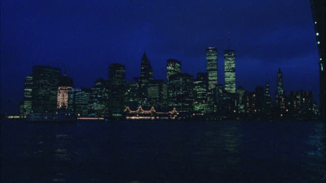 wide angle of skyscraper and high rise office, apartment and condominium buildings of new york city skyline. world trade center, twin towers. river ferry or boat moves from left to right on east river past camera. lights. midtown manhattan. - world trade center manhattan video stock e b–roll
