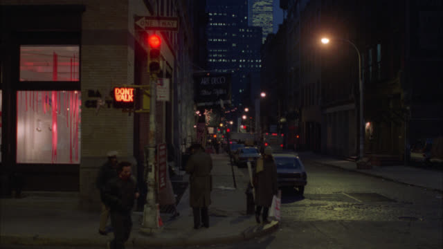 vídeos de stock e filmes b-roll de wide angle of street corner with stop light in city. pedestrians, people walking on sidewalk, across street. cars driving, parked on side of streets. multi-story brick buildings on both sides of street. high rise buildings in bg. could be in soho. - 1985