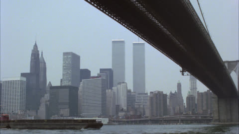 stockvideo's en b-roll-footage met wide angle of new york city skyline from under brooklyn bridge. world trade center or twin towers visible. waterfront. east river runs under bridge. barges or freighter moves under bridge. preview file has been trimmed. full clip available by calling sony - world trade center manhattan