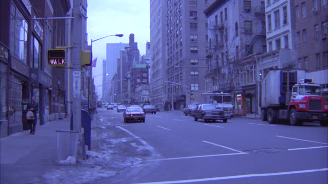 pan right to left of cars driving down nyc street. camera follows white cadillac down middle class residential street and then pans up to multi-story apartment building.  winter. - new york city stock videos & royalty-free footage