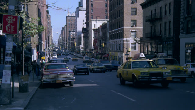 pan right to left of traffic driving down new york street as mustang turns corner and parks in front of stone apartment building. upper or middle class. taxis. could be residential area. man exits car and climbs steps of apartment building. - new york city 1970s stock videos & royalty-free footage