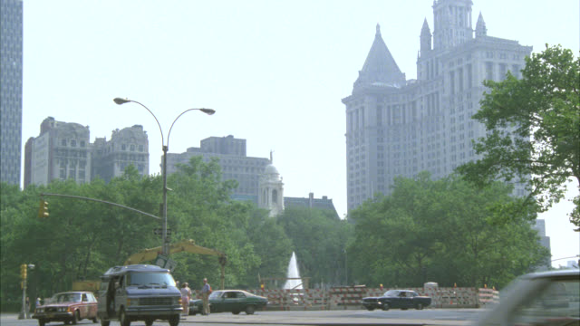 """wide angle of mid-town apartment building near central park. cars and traffic stopped near fountain. mustang drives by and parks at curb. camera zooms in on sign reading """"don't even think of parking here."""" man exits car. - central park manhattan stock videos & royalty-free footage"""