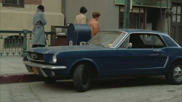 pan up from blue ford mustang car parked on city street to white brick apartment building with fire escapes. mailbox. taxis. - ford mustang stock videos and b-roll footage