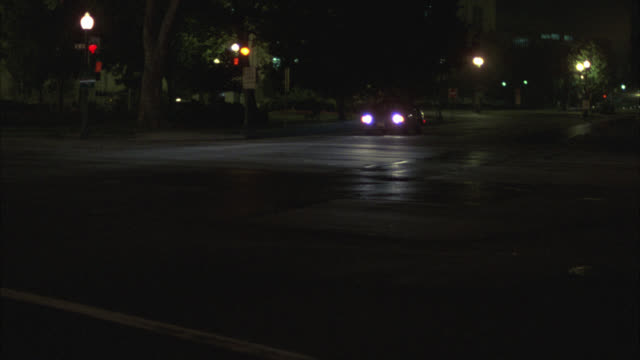 wide angle of a car driving on a washington dc city street towards the capitol building. street lamps are on. capitol building is lit up. domed building. - washington dc stock-videos und b-roll-filmmaterial