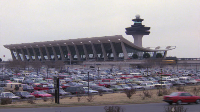 wide angle of dulles airport control tower, futuristic terminal and parking lot filled with cars. - dulles international airport stock videos and b-roll footage