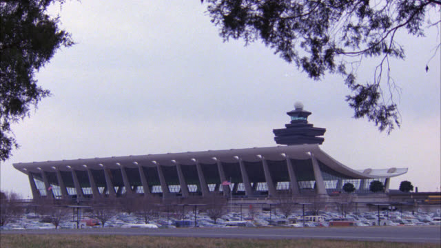 wide angle of dulles airport control tower, futuristic terminal and parking lot filled with cars. cars drive by on street in fg. - dulles international airport stock videos and b-roll footage