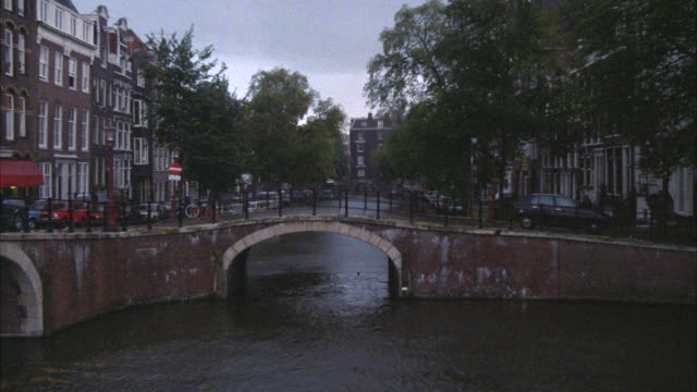 vidéos et rushes de wide angle of bridge over canal in amsterdam. trees and multi-story brick buildings, could be middle class apartment buildings, shops or restaurants on both sides of canals. sky is cloudy or overcast. europe. - amsterdam